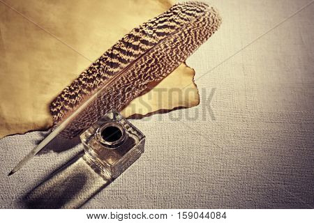 Feather pen and inkwell on sackcloth background