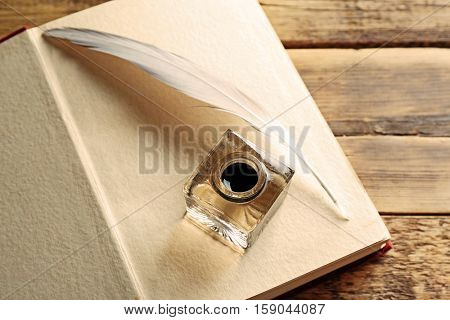 Feather pen with inkwell and open notebook on wooden background