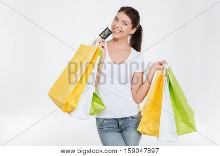 Picture of happy young woman dressed in white t-shirt holding purchasings and credit card after shopping. Isolated over white background. Look at camera.