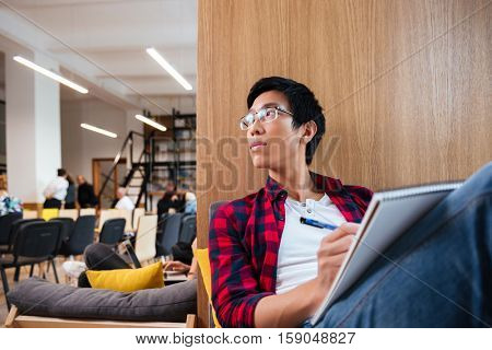 Concentrated asian student studying in university library sitting on sofa. Looking aside.