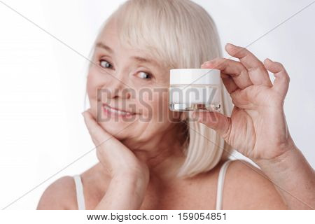 Facial care. Happy cheerful nice woman holding a cream bottle and smiling while using cosmetics