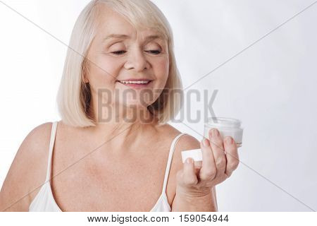Moisture cream. Positive pleasant senior woman holding a cream bottle and looking at it while intending to use it