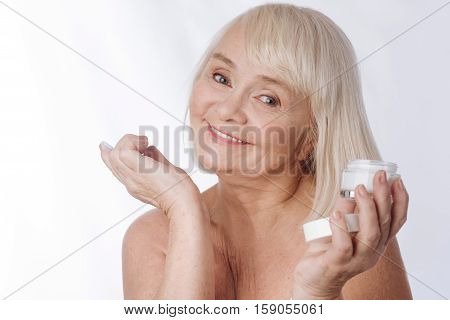 Facial cosmetics. Happy pleasant grey haired woman looking at you and smiling while holding a facial cream bottle