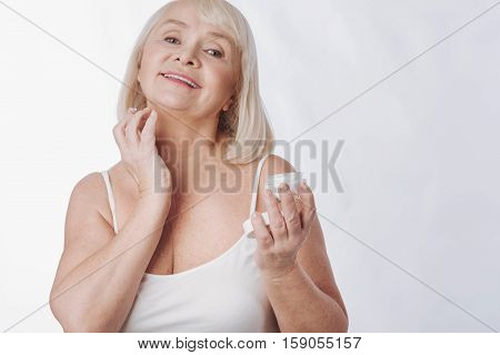 Skin care. Pleasant nice elderly woman holding up her head and putting cream on the neck while holding an anti age cream bottle