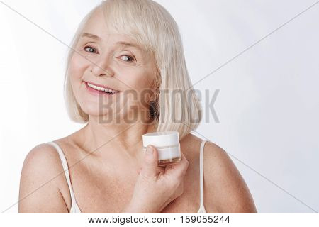 Be always young. Pleasant positive elderly woman holding a bottle of anti age cream and smiling while fighting with wrinkles