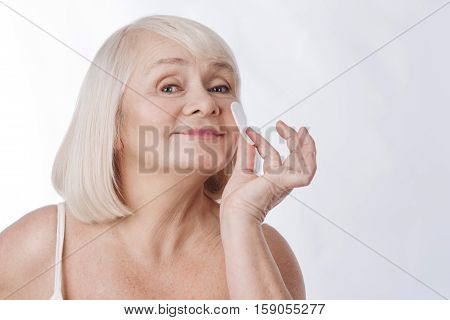 Facial cleansing. Delighted joyful elderly woman holding a cotton pad and pressing it to her cheek while cleaning her skin
