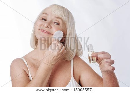 Skin lotion. Nice delighted aged woman holding a bottle of lotion and using a cotton pad while cleaning her face
