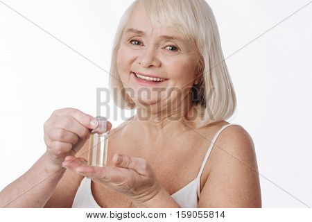 Bottle of skin lotion. Smiling positive aged woman holding a bottle of skin lotion on her palm and opening it while using cosmetics