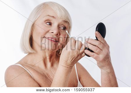 I need to see my face. Positive happy senior woman holding a mirror and looking at her face while using a cotton swab