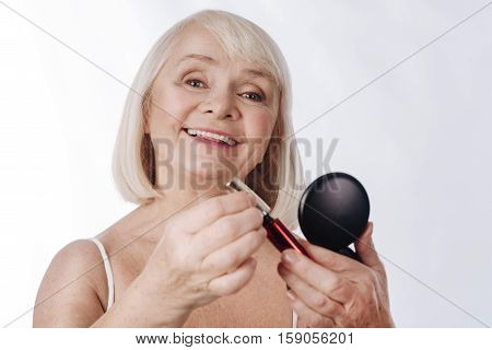Decorative cosmetic products. Pleasant cheerful elderly woman holding mascara and smiling while using decorative cosmetics