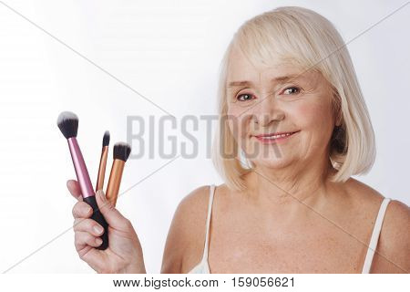 Makeup brushes. Good looking delighted elderly woman holding cosmetic tools and smiling while preparing to put on make up