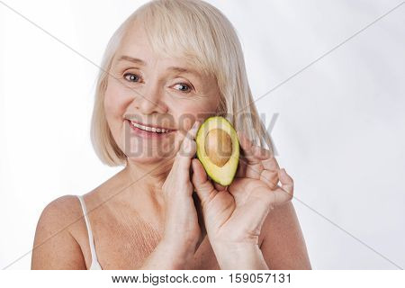 Giving energy. Delighted smiling senior woman holding an avocado half and touching it while looking at you