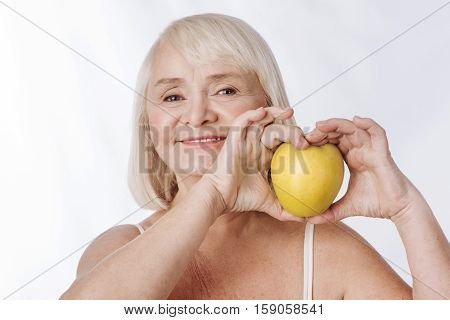 Useful vitamins. Pleasant optimistic retired woman looking at you and having a big yellow apple in her hands while feeling happy