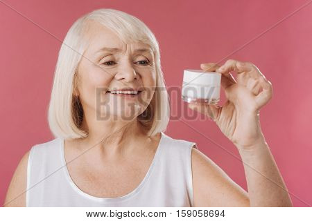Anti aging skin products. Pleasant charming senior woman holding a bottle of skin lifting cream and looking at it while using anti age cosmetics
