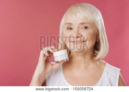 Fighting with wrinkles. Positive elderly grey haired woman standing against pink background and holding a bottle of cream while fighting with the age
