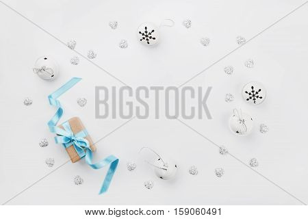 Christmas gift box with blue ribbon and jingle bell on white table from above. Holiday greeting card. Mockup. Flat lay frame.