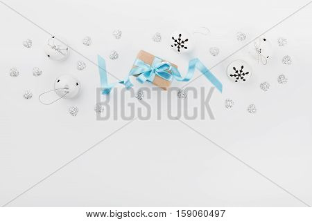 Christmas gift box with blue ribbon and jingle bell on white background from above. Holiday greeting card. Mockup. Flat lay border.
