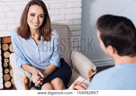 Rise your mood. Cheerful delighted elated woman sitting in the arm chair and smiling while talkign with her psychologist