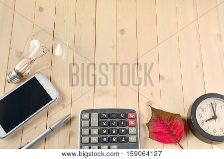 Bulb smart phone silver pen calculator red leaf and clock on the table.