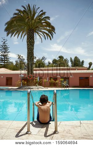 Young Boy Enjoying Vacation at Tropical Swimming Pool in Arequipa Peru.