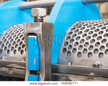 Detail photo of twin screw industrial press for processing of food byproducts.
