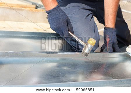 Roofer builder worker finishing folding a metal sheet using rubber mallet
