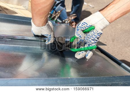 Roofer folding a metal sheet using special pliers with a large flat grip