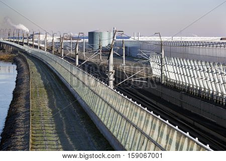 Railroad track in industrial area with greenhouses in the Netherlands