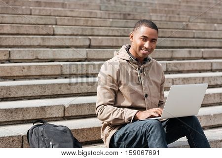 Photo of young african cheerful man sitting on staircase and using laptop. Looking at camera.