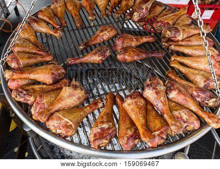 BBQ turkey legs on a large grill.
