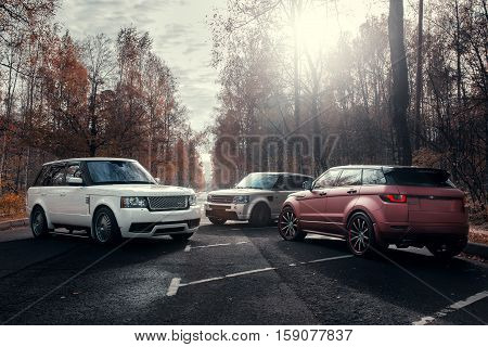 Moscow, Russia - October 23, 2016: Three cars Land Rover Range Rover parked at autumn forest asphalt road at sunny daytime