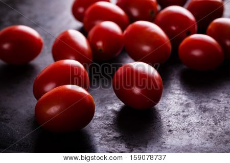 Several Red Cherry Tomatoes On Black Board
