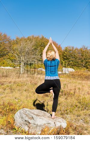 Young woman in tree yoga pose standing on one leg on rock