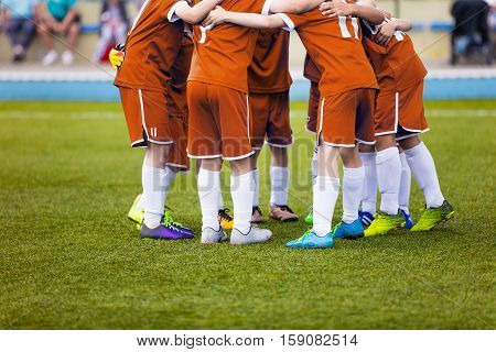 Young football soccer players in orange sportswear. Young sports team on pitch. Pep talk before the final match. Soccer school tournament. Children on sports field