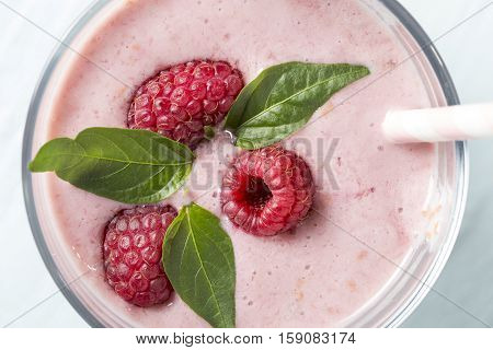Top view of a raspberry smoothie glass set on a wooden boards decorated with drinking straw three raspberries and mint leaves. Selective focus