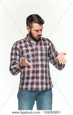 Man wearing a checkered shirt is looking serious with and holding imaginary object in his hands. Over white background