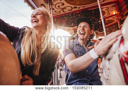 Young man and two women on carousel at fairground. Young couple riding horse carousel in amusement park and laughing.