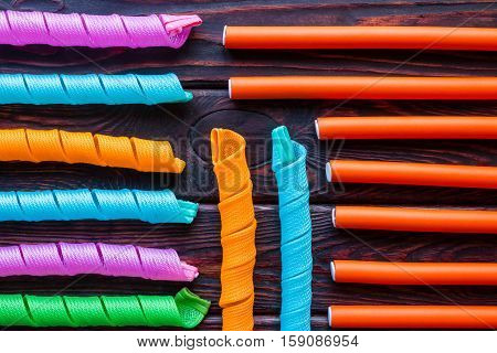 Multicolored Hair Curlers On A Wooden Background