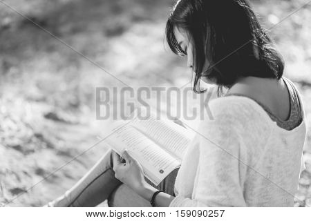 A young woman reading a book. Book in woman hands black and white.