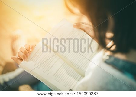 A young woman reading a book. Book in woman hands sunset vintage tone
