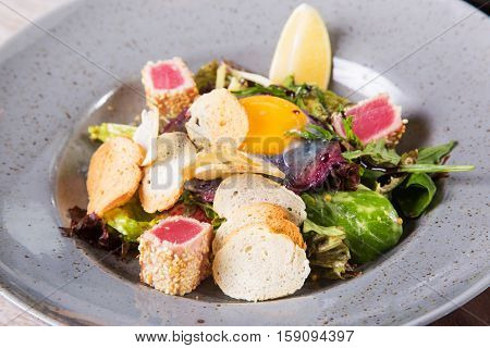 salad with fresh tuna and yolk,vegetables mixed in grey dish