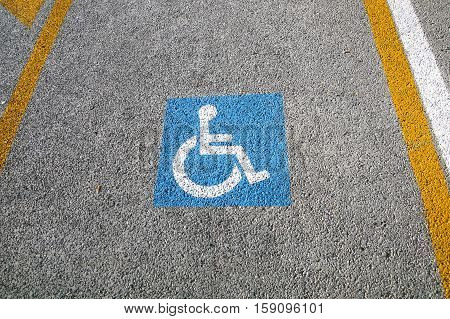 disabled parking permit sign painted on the street .