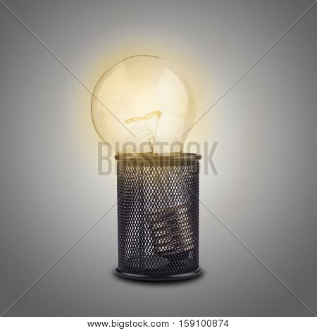 Concept for creativity and ideas with a bright light bulb standing in a pencil holder on grey background