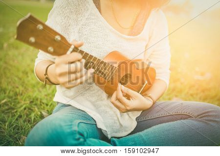 .young Woman Playing On Ukulele