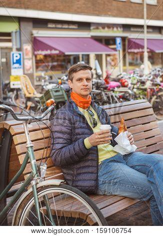 Tourist having take-away breakfast  in the street of Amsterdam