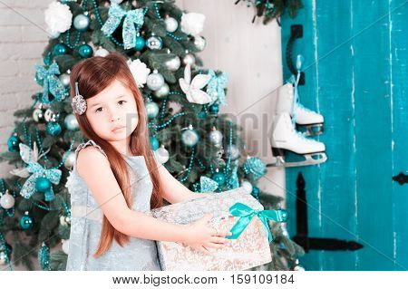 Child girl 3-4 year old holding christmas gift over christmas tree in room. Looking at camera. Merry christmas. Celebration. Playful.