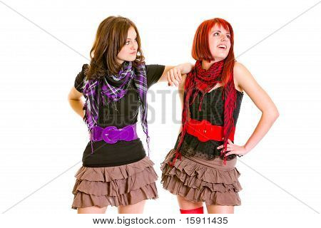 Confused young girl put hand on shoulder her pleased girlfriend and looking on her isolated on white