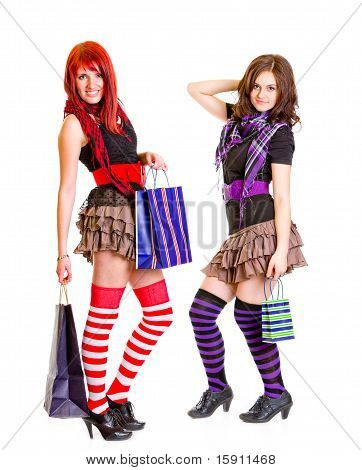 Two young pleased girlfriends standing with shopping bags in hands isolated on white