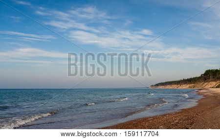 landscape with views of the Baltic Sea, on the banks of large and small stones and sand, small waves and endless horizon, blue sky and bright water, distant cliff with pine trees