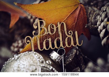 the text bon nadal, merry christmas in catalan, made in wooden and some dry leaves, some pine cones and an ornamented christmas ball